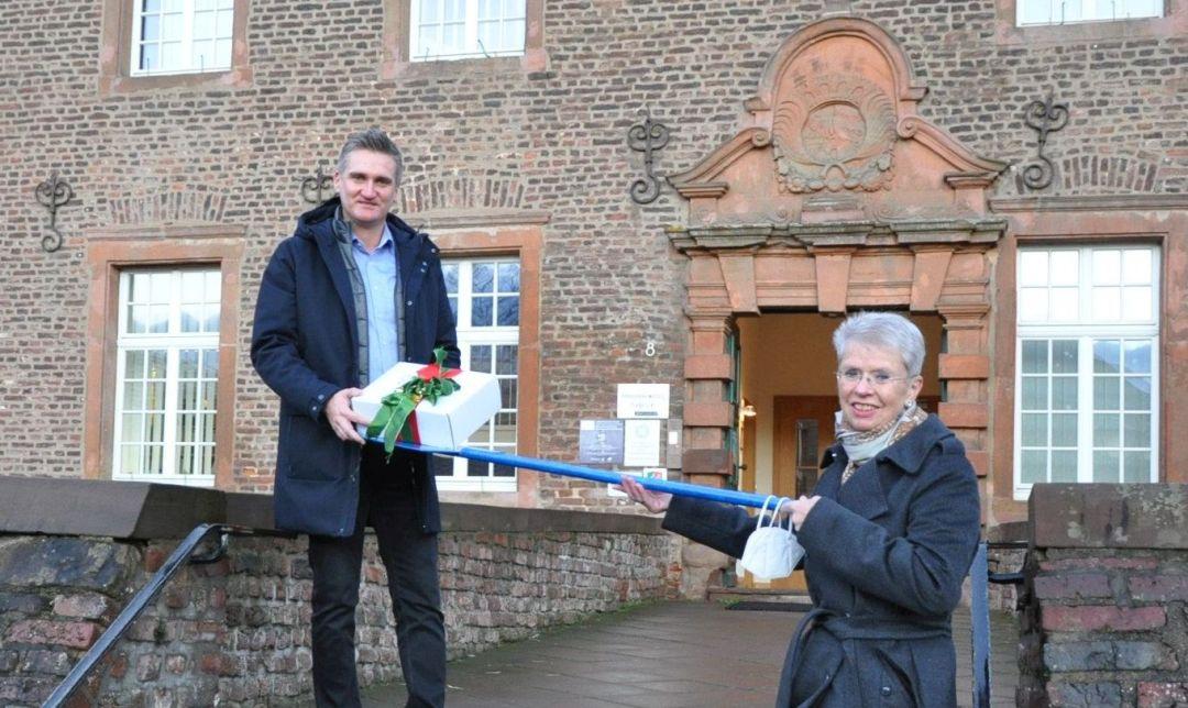 Marie-Theres Innecken-Prüss übergibt dem Niederzierer Bürgermeister Frank Rombey symbolisch ein Weihnachtspaket.